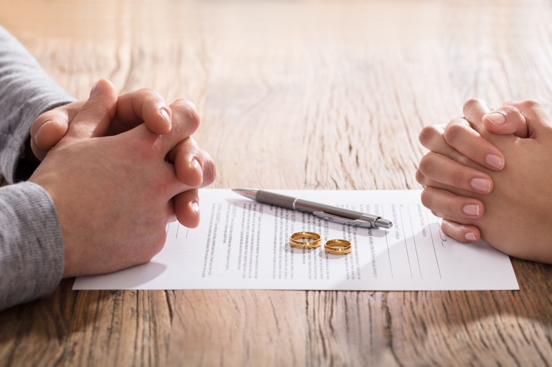 Hands Of Wife And Husband On Divorce Document With Wedding Ring In The Center