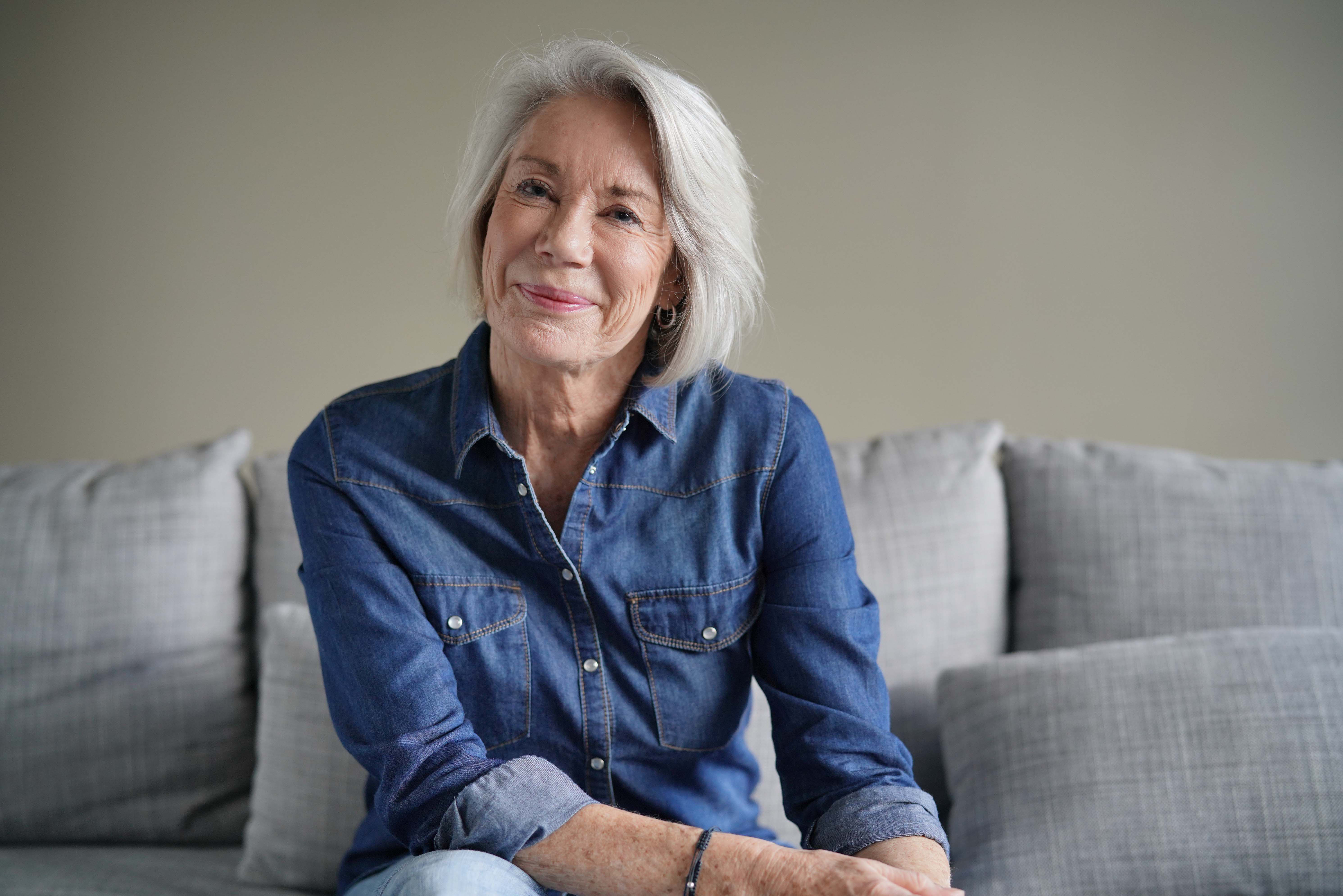 Portrait of modern senior woman in all denim on couch