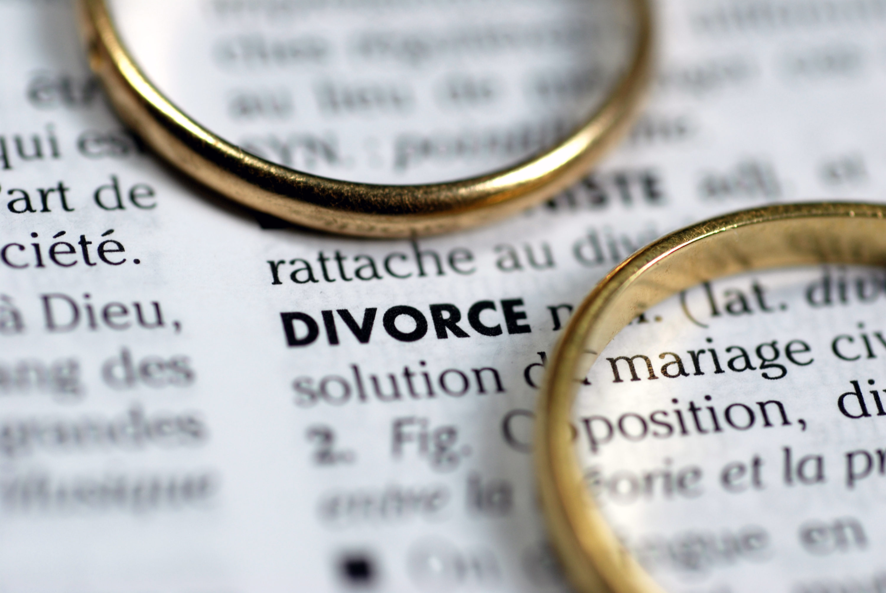 two wedding rings on top of a sheet with information about divorce