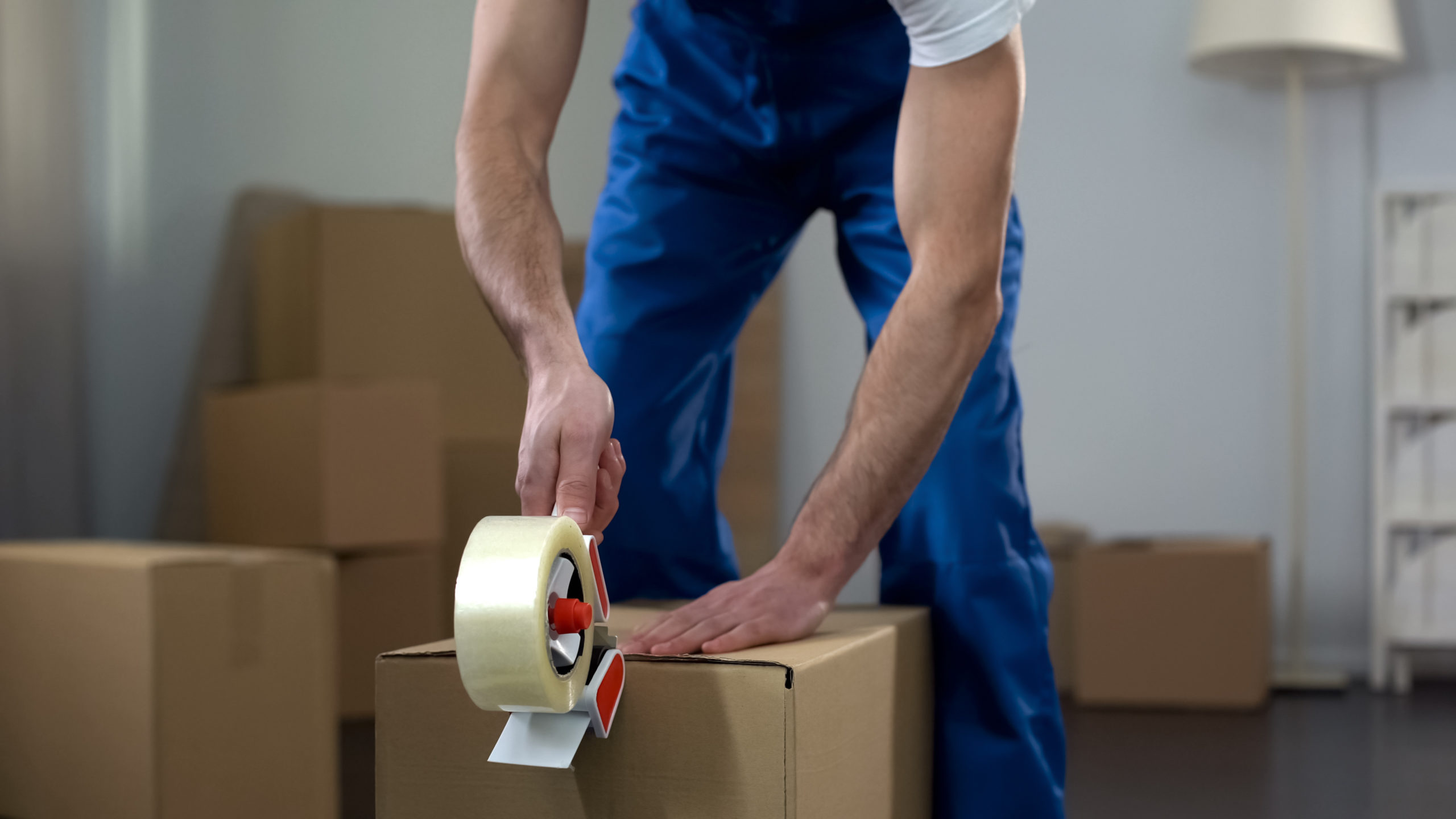 Child relocation concept. Moving company worker packing cardboard boxes, quality delivery services.