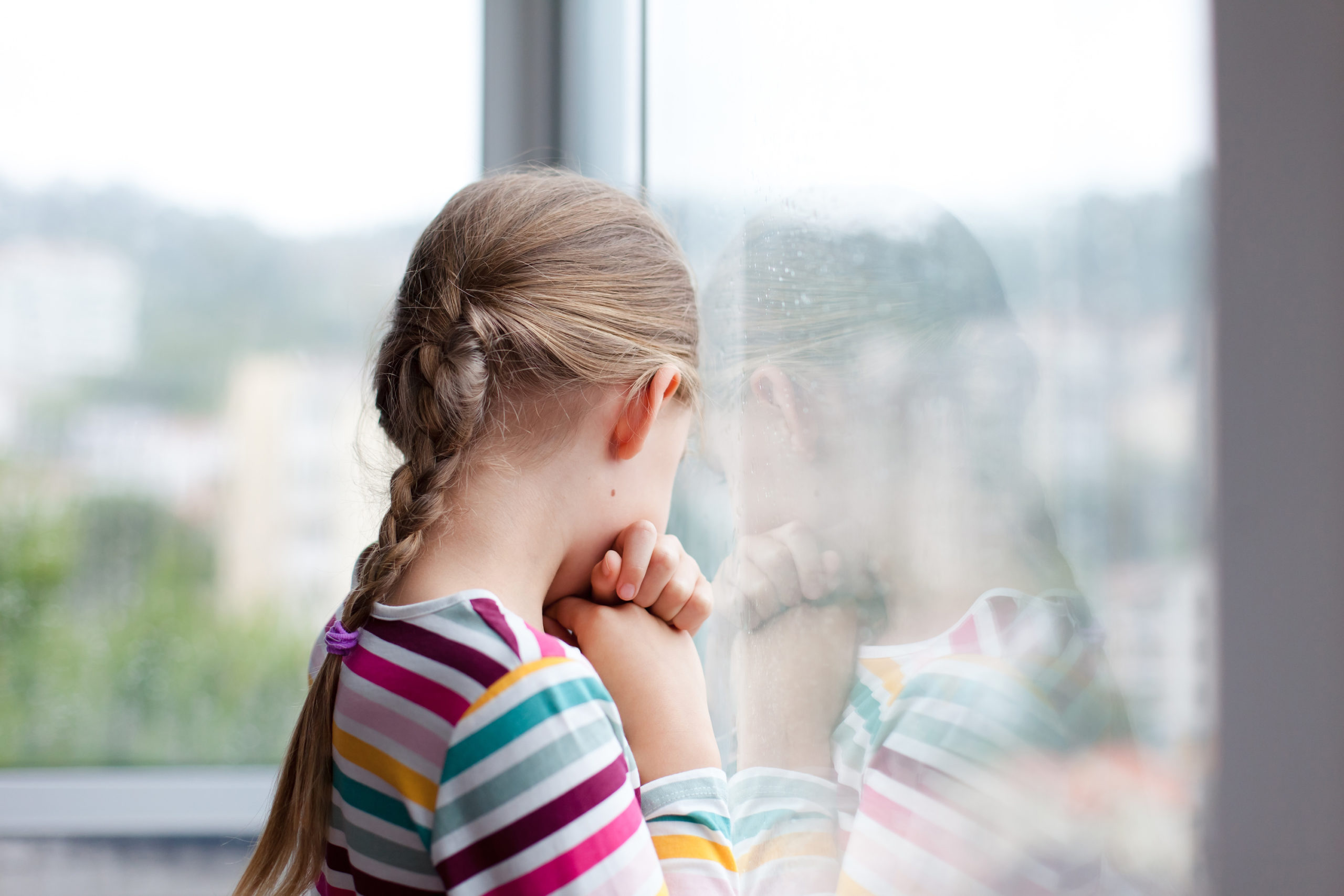 Withholding child visitation concept. Sad child looking through rainy window at home. Upset kid in self isolation during quarantine.