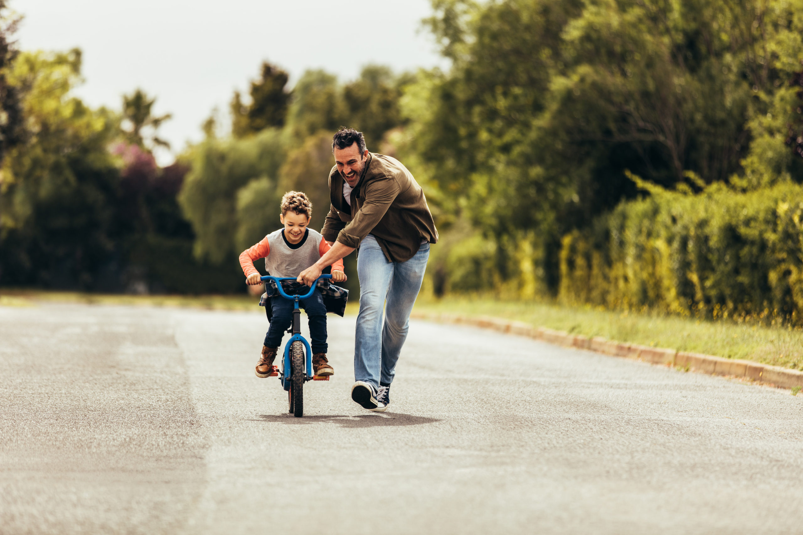 child custody order concept. Father teaching his son to ride a bicycle.